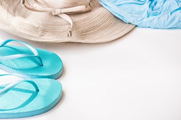 白い背景の上の青いフリップフロップ麦わら帽子ビーチラップ