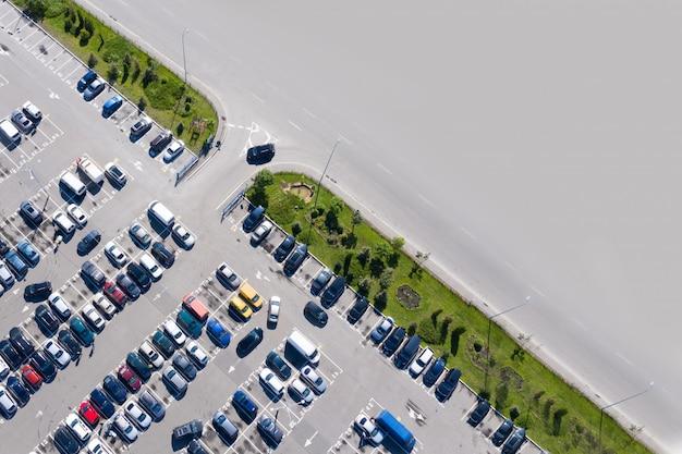 テキスト用のスペースを持つデザインのパターン:駐車場。駐車場には色とりどりの車がたくさん。ドローンからの撮影。