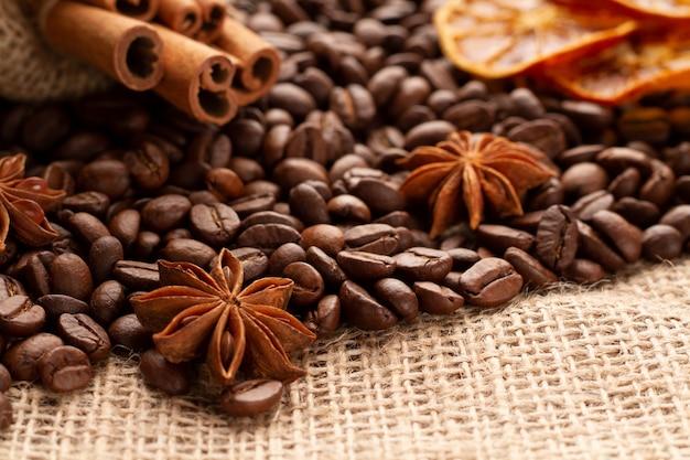 アニスまたはバディアンは、天然風味のシナモンスティックと共にコーヒー豆の上にあります。コーヒーのコンセプトです。