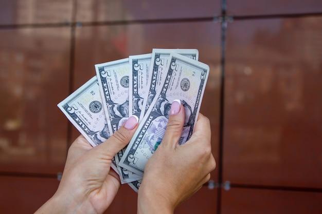 女性は茶色の背景に対して彼女の手のひらでそれらを扇形に、ドル札を数える