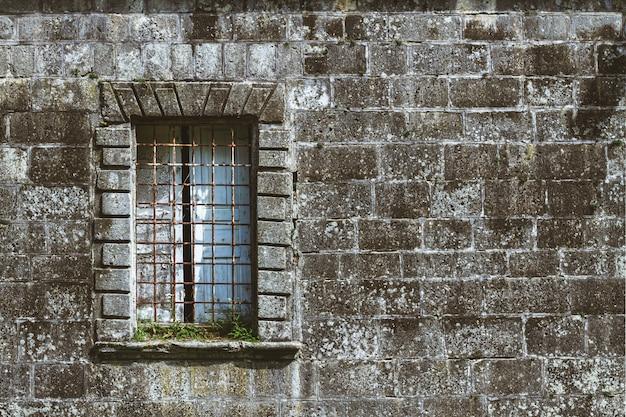Каменная темная стена древнего замка с окном и решеткой. античная темная кладка стены замка. средневековый каменный рыцарский замок с решетками на окне.