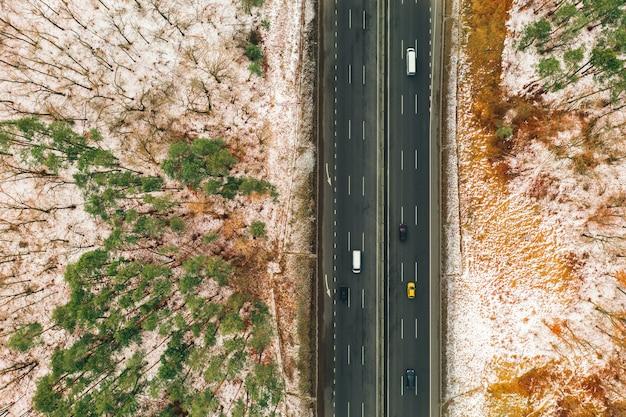 車上面と田舎道のプロットのドローン写真。冬の森と風景の木々の間でアスファルト道路の車