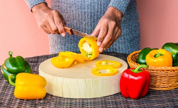 Женский шеф-повар резки перец на разделочной доске