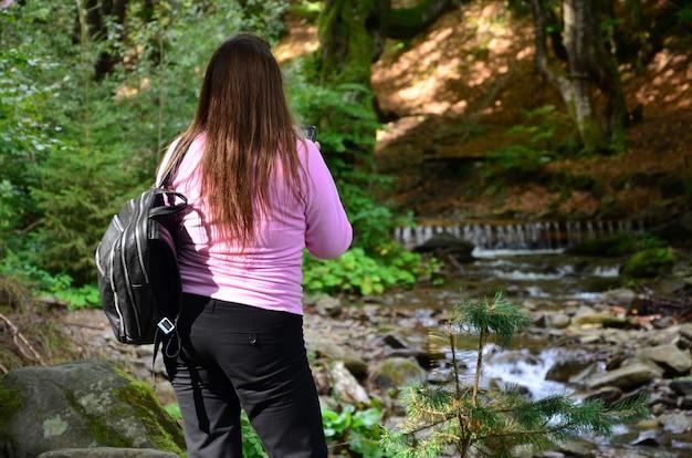 濃い色のズボンとピンクのスウェットシャツを着た女性が山の川を賞賛します