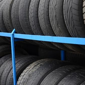 自動車店でいろいろな車のタイヤが付いている棚。多くの黒いタイヤ。