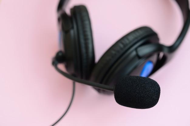 音楽リスニングのコンセプトです。黒のヘッドフォンはピンクの背景にあります。