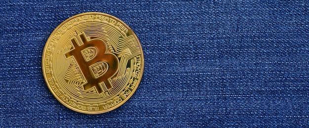 ゴールデンビットコインはブルージーンズ生地にあります。新しいバーチャルマネー。コインの形の新しい暗号通貨