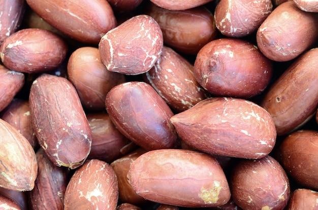落花生。茶色の皮と小さな黄色いナッツがたくさん。背景テクスチャ