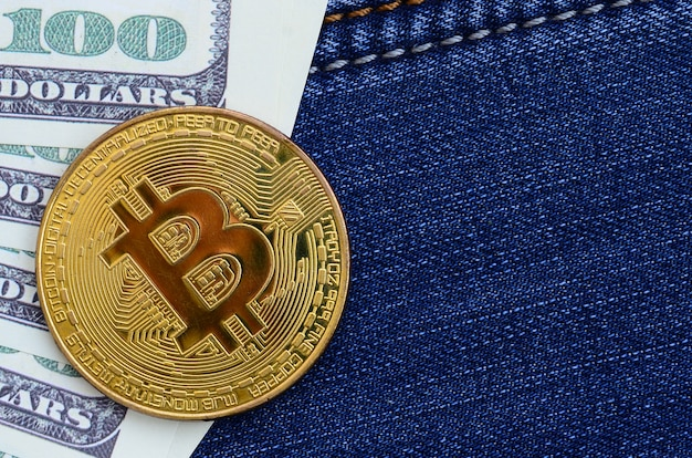 ゴールデンビットコインとドル紙幣はブルージーンズ生地にあります。新しいバーチャルマネー。コインの形の新しい暗号通貨