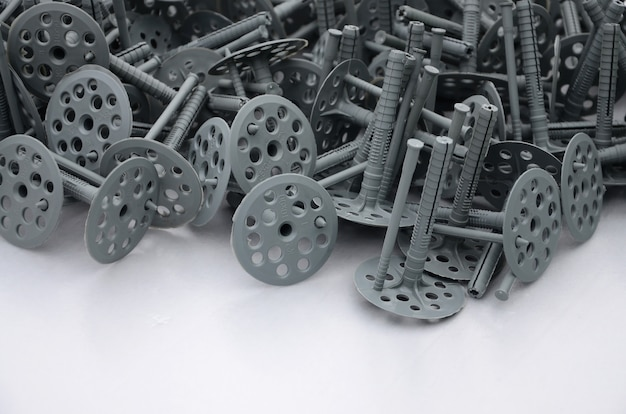 断熱のための多くの灰色のプラスチック製ダボ(固定)の背景