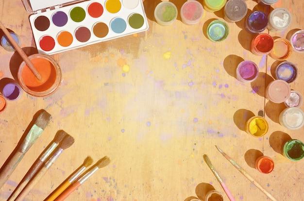 多くのブラシと水彩画とガッシュ塗料の瓶のある静物