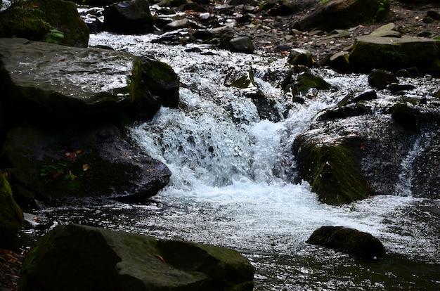 山の石の間の水の短い流れの形で小さな野生の滝のクローズアップ画像