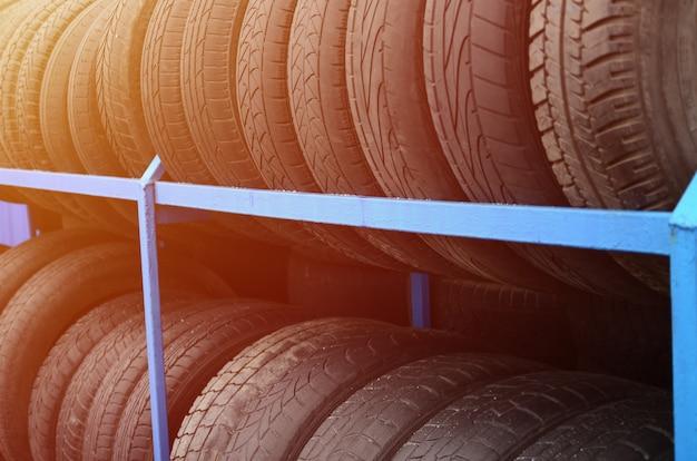 自動車店でいろいろな車のタイヤが付いている棚。多くの黒いタイヤ。タイヤスタックの背景。セレクティブフォーカス