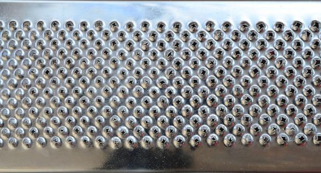 金属クロムおろし金のクローズアップの断片。食品を粉砕するためのブレードのテクスチャ