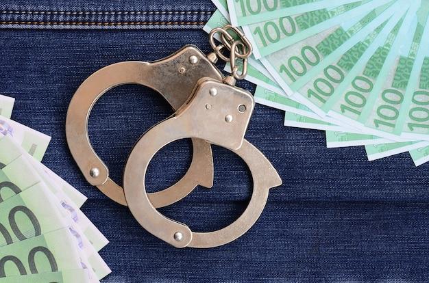 ユーロ紙幣や警察の手錠の多くのファンは暗いデニムの表面にあります。背景イメージ