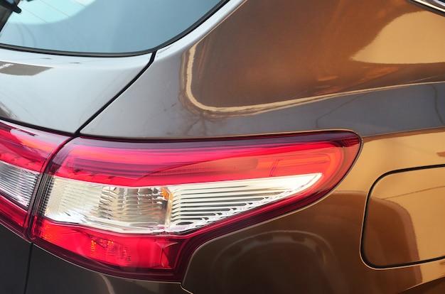 茶色の乗用車のクローズアップの赤いテールランプ。詳細写真
