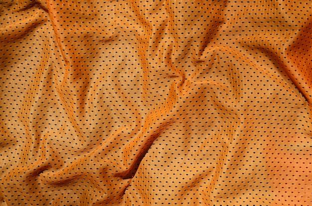 オレンジ色のスポーツ服生地テクスチャ背景。上面図