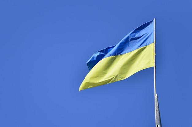 青い雲一つない空に対してウクライナの旗。公式の旗