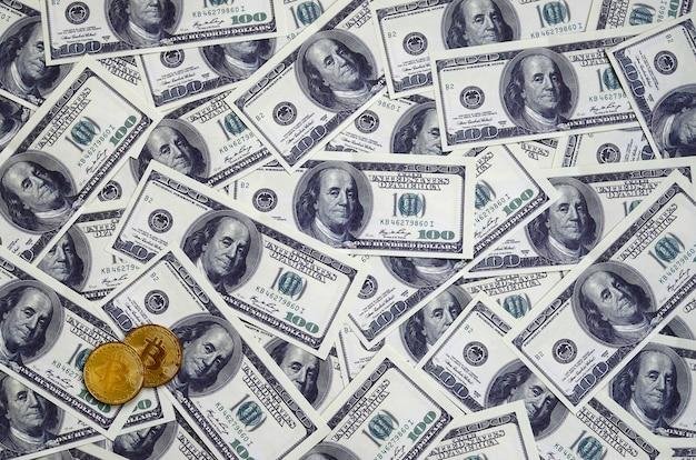 Золотые биткойны лежат на множестве долларовых купюр.
