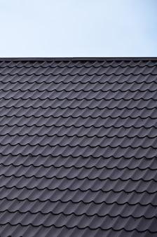 塗装金属の屋根の質感。傾斜屋根の屋根カバーのクローズアップ詳細図。