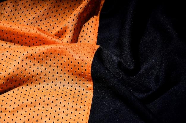 スポーツ服の生地のテクスチャ背景、オレンジ色の布の繊維表面のトップビュー