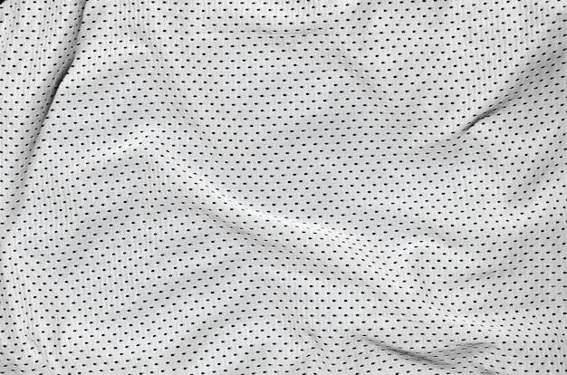 織り目加工の背景を作成する白いポリエステルナイロンスポーツウェアパンツのクローズアップ