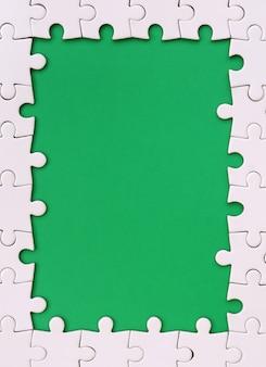 緑のスペースの周りに白いジグソーパズルで作られた、長方形の形でフレーミング