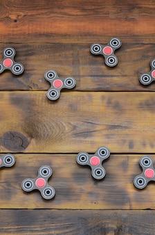 Редкие деревянные непоседы ручной работы лежат на коричневой деревянной поверхности. модные игрушки для снятия стресса