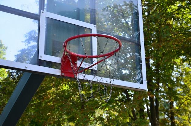 澄んだ青い空と屋外のバスケットボールのバックボード