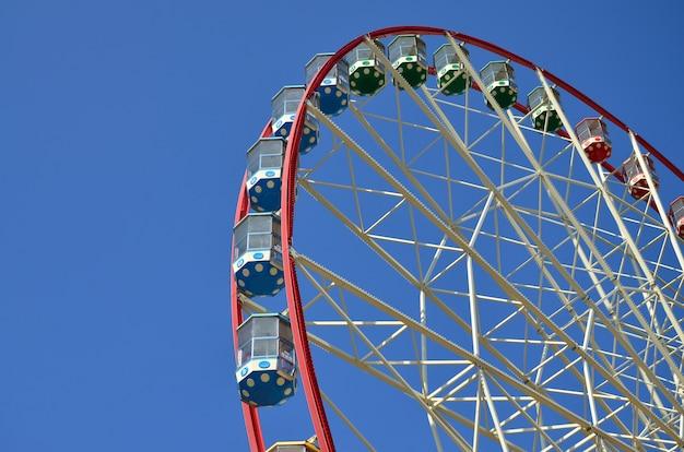 きれいで青い空を背景に大きくてモダンな多色観覧車