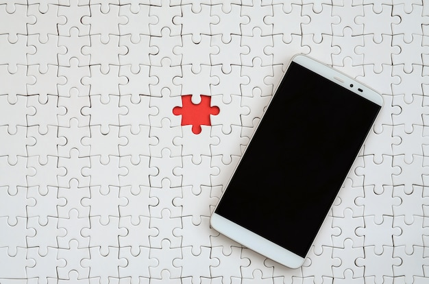 タッチスクリーンを備えた現代の大きなスマートフォンは、組み立てられた状態で白いパズルの上にあります