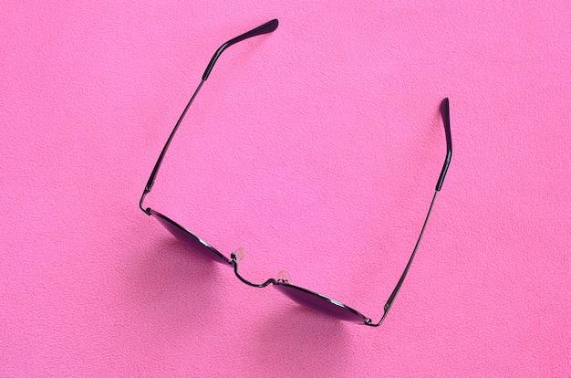 丸いメガネとスタイリッシュな黒いサングラスは毛布にあります。