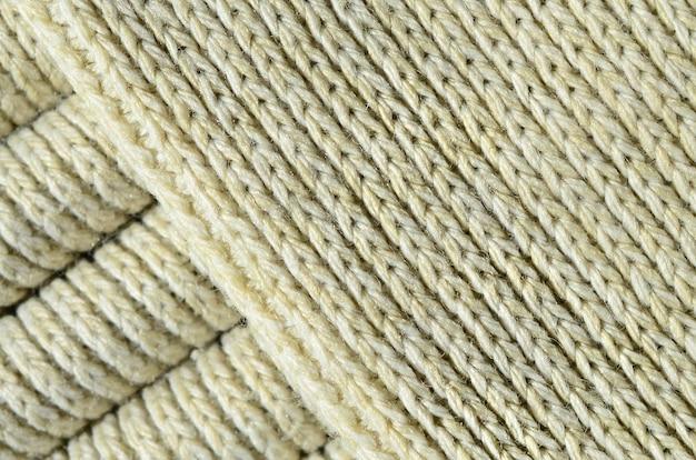 柔らかい黄色のニットセーターの組成。糸のバインディングのマクロテクスチャ