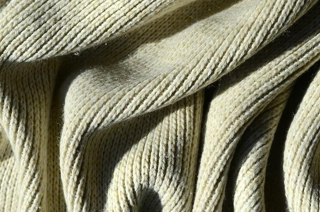 柔らかい黄色のニットセーターの布の質感。糸の束縛構造のマクロ画像