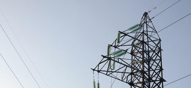 青い空を背景に電力線タワー