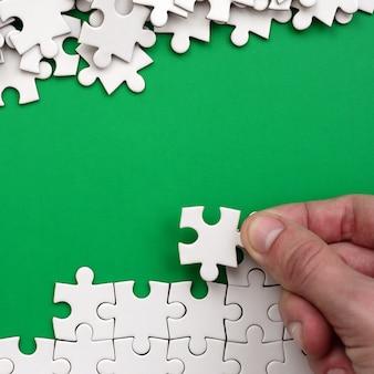 手は白いジグソーパズルと裸のパズルのピースの山を折ります