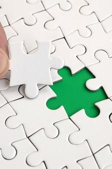 人間の手はジグソーパズルから表面の最後の行方不明の要素を埋めます