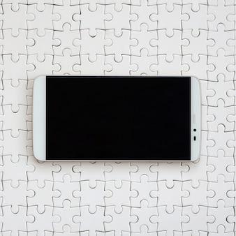 タッチスクリーンを備えた現代の大きなスマートフォンは組み立てられた状態で白いジグソーパズルの上にあります