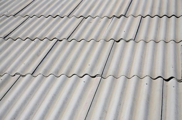 Фрагмент серой шиферной крыши старого образца из асбестового материала.