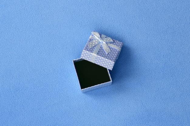 小さな弓と青で小さなギフトボックスを開く