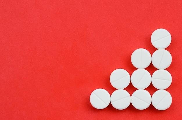 明るい赤の背景にいくつかの白い錠剤