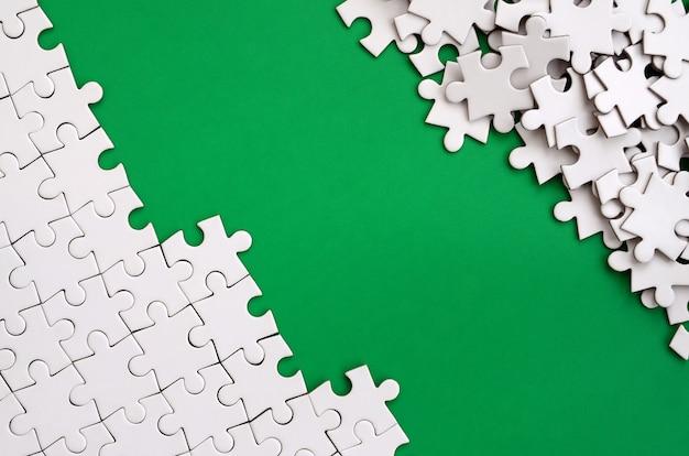 折り畳まれた白いジグソーパズルの断片と裸のパズルの山