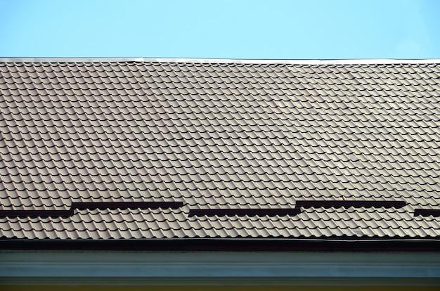 濃い赤色の金属タイルからの屋根の断片。品質の屋根