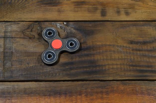 Редкий деревянный непоседа ручной работы лежит на коричневой деревянной поверхности