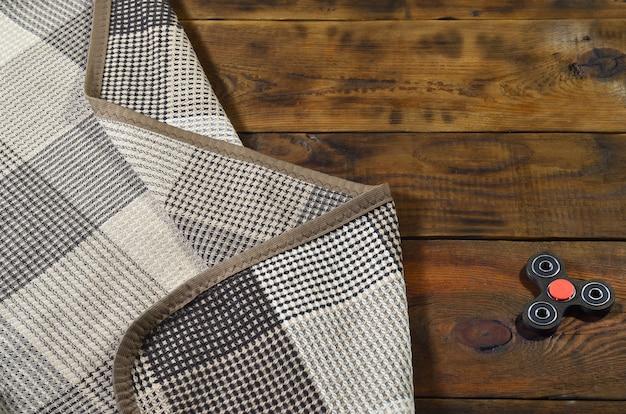 Редкий деревянный блесна ручной работы лежит на клетчатом пледе на коричневой деревянной поверхности фона