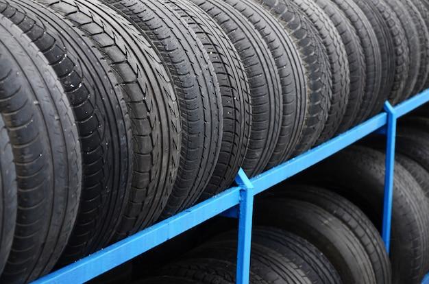 自動車店でいろいろな車のタイヤが付いている棚。多くの黒いタイヤ。タイヤスタックの背景