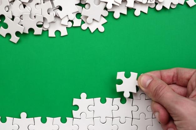 手が白いジグソーパズルを折ると裸のパズルのピースの山が緑の表面の背景にある