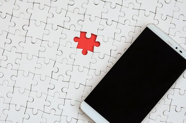 タッチスクリーンを備えた現代の大きなスマートフォンは、組み立てられた状態で白いパズルパズルの上にあります