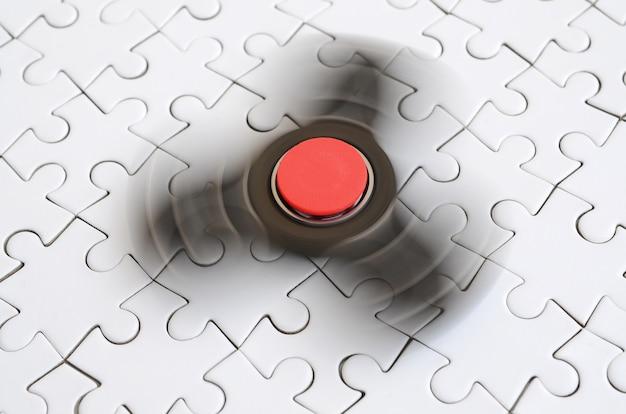 木製のスピナーが白いジグソーパズルの背景に回転します。