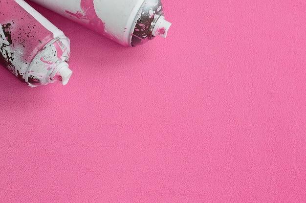 ペンキのしずくが入っているいくつかの中古のピンクのエアロゾルスプレー缶は、柔らかく毛皮のような淡いピンクのフリース生地の毛布の上にあります。